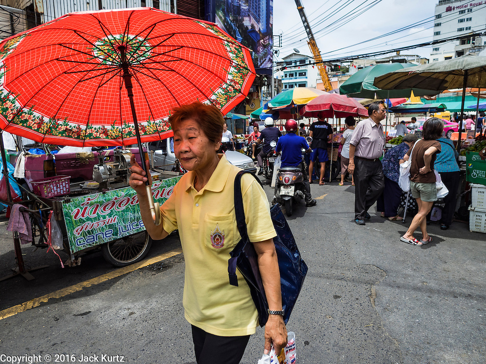 08 JUNE 2016 - BANGKOK, THAILAND:  A woman walks through the small produce market at the intersection of Phlap Phla Chai and Chareon Krung Streets in Bangkok's Chinatown neighborhood. The Bangkok Metropolitan Rapid Transit (MRT) system, Bangkok's subway, is being expanded through Chinatown and a station is under construction at the intersection. The small produce market at the intersection will have to move and several of the businesses near the intersection have been evicted to make way for the construction. Bangkok's Chinatown, considered by some to be one of the best preserved Chinatown districts in the world, is changing. Many of the old shophouses are being demolished and replaced by malls and condominium developments.     PHOTO BY JACK KURTZ