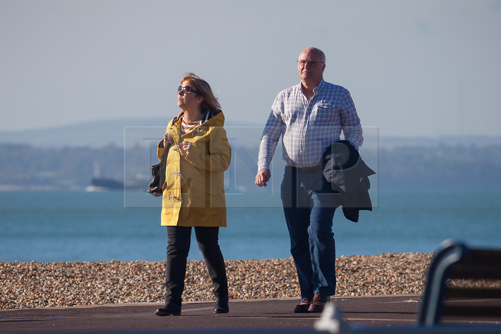 © Licensed to London News Pictures. 27/10/2017. Portsmouth, UK.  A couple taking a stroll whilst enjoying the sunny autumn weather along Southsea promenade today, 27th October 2017.  Photo credit: Rob Arnold/LNP