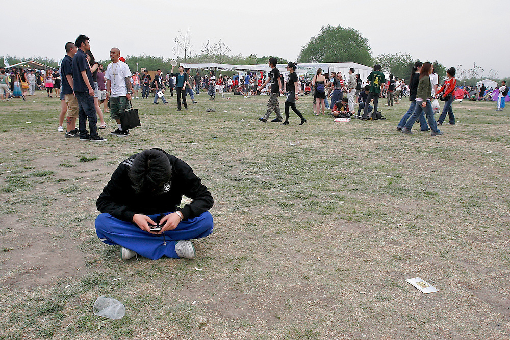 Texting in the open area between stages at the Midi Festival in Beijing China 2007.  Midi is an  rock music festival held in northern Beijing catering to a small group of music listeners in China.  The festival lasts 4 days and gives performances from Chinese and international bands.