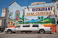 Mural on a  Mexican restaurant in Los Angeles with a limousine out in front.