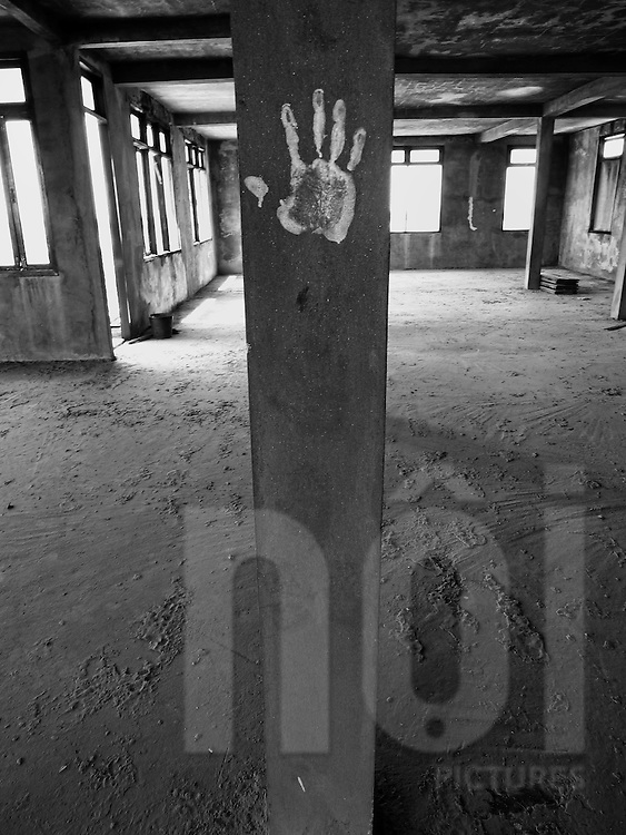 Decay interior of a house at Nam Phu before demolition,  Vientiane, Laos, Asia. A hand is paint on a concrete pillar