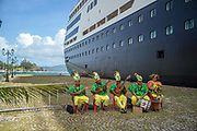 Traditional musicians serenade passengers disembarking from a cruise ship in the port of Uturoa on the Island of Raiatea, French Polynesia.