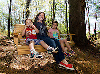 James, Deanna and Ellie Donnelly enjoy a swing and a song in the Natural Playscape at Prescott Farm on Saturday morning during their grand opening celebration.  (Karen Bobotas/for the Laconia Daily Sun)