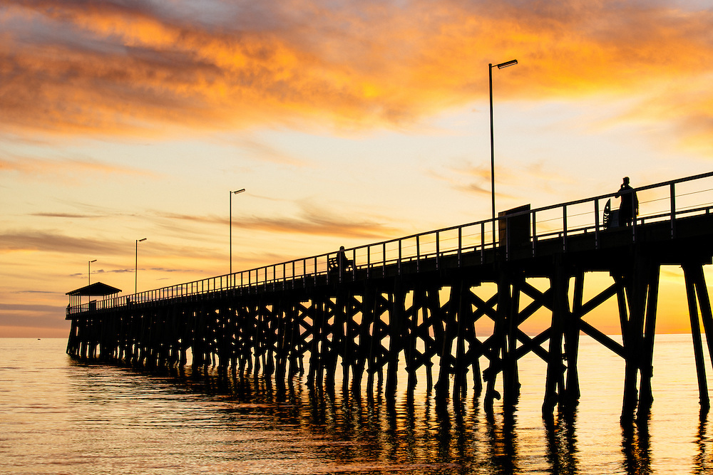 Silhouette showing the structure of the Grange Jetty in the calm waters of Gulf St Vincent with vibrant colours of the sun setting behind. Adelaide.