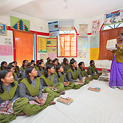 CAPTION: The trainer is teaching the girls about the menstrual cycle, what it means for them, and how they can take care of their needs after it begins. LOCATION: Mahila Samakhya, Ratu (block), Ranchi (city), Jharkhand (state), India. INDIVIDUAL(S) PHOTOGRAPHED: Adult: Rajni Lakra; children: multiple people.