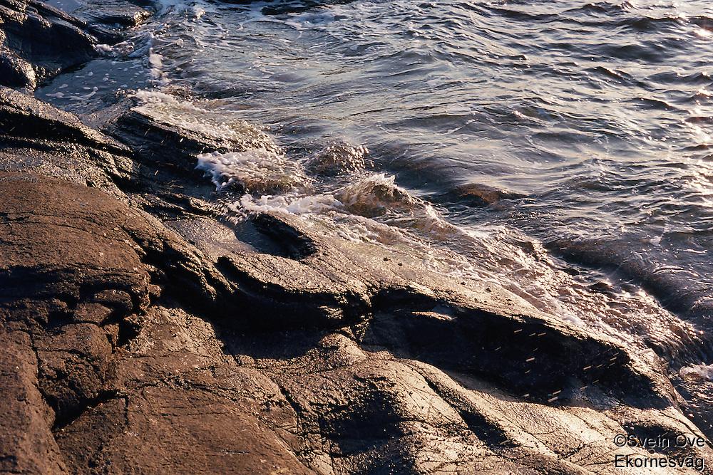 Solen speiler seg i sjøen ved svabergene på Vigra i solnedgangen.<br /> Foto: Svein Ove Ekornesvåg