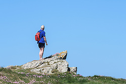 A tourist standing on a rock on East Pentire Headland in Newquay, Cornwall.