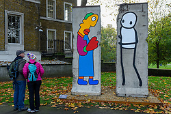 © Licensed to London News Pictures. 05/11/2019. LONDON, UK.  Passers-by view new work by artists Theirry Noir (L) and STIK (R) on original Berlin Wall sections to mark 30 years since the fall of the Berlin Wall.  Located outside the Imperial War Museum, the new works reflect the symbolic connections between the Berlin Wall and street art and the fall of the wall on 9 November 1989.  These new works are on display until 1 December.  Photo credit: Stephen Chung/LNP