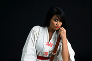 Young Asian woman wielding a bokken (a wooden Japanese sword used for practice) on black background
