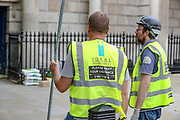 """Please keep your distance 2 meters,"" says in the back of a worker from ""Ideal Installations"" working in London's Whitehall Building on Wednesday, May 27, 2020. The prime minister's populist appeal has been hammered by the news that, as the coronavirus outbreak raged, chief adviser Cummings drove 250 miles (400 kilometres) to his parents' house while he was falling ill with suspected COVID-19 allegedly flouting lockdown rules that the government had imposed on the rest of the country. (Photo/ Vudi Xhymshiti)"