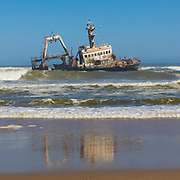 """The Skeleton Coast is the northern part of the Atlantic Ocean coast of Namibia and south of Angola from the Kunene River south to the Swakop River, although the name is sometimes used to describe the entire Namib Desert coast. The Bushmen of the Namibian interior called the region """"The Land God Made in Anger"""", while Portuguese sailors once referred to it as """"The Gates of Hell"""".<br /> <br /> The name Skeleton Coast was invented by John Henry Marsh as the title for the book he wrote chronicling the shipwreck of the Dunedin Star. Since the book was first published in 1944 it has become so well known that the coast is now generally referred to as Skeleton Coast and is given that as its official name on most maps today.<br /> <br /> The Suiderkus (1976): A relatively modern fishing trawler, the Suiderkus ran aground near Möwe Bay on her maiden voyage despite a highly sophisticated navigational system. After a few months most of the ship had disintegrated but a large portion of the hull survived. The hull is home to cormorants, and it's a popular subject for photographers. It's one of the most visible and relatively accessible wrecks along the coast."""