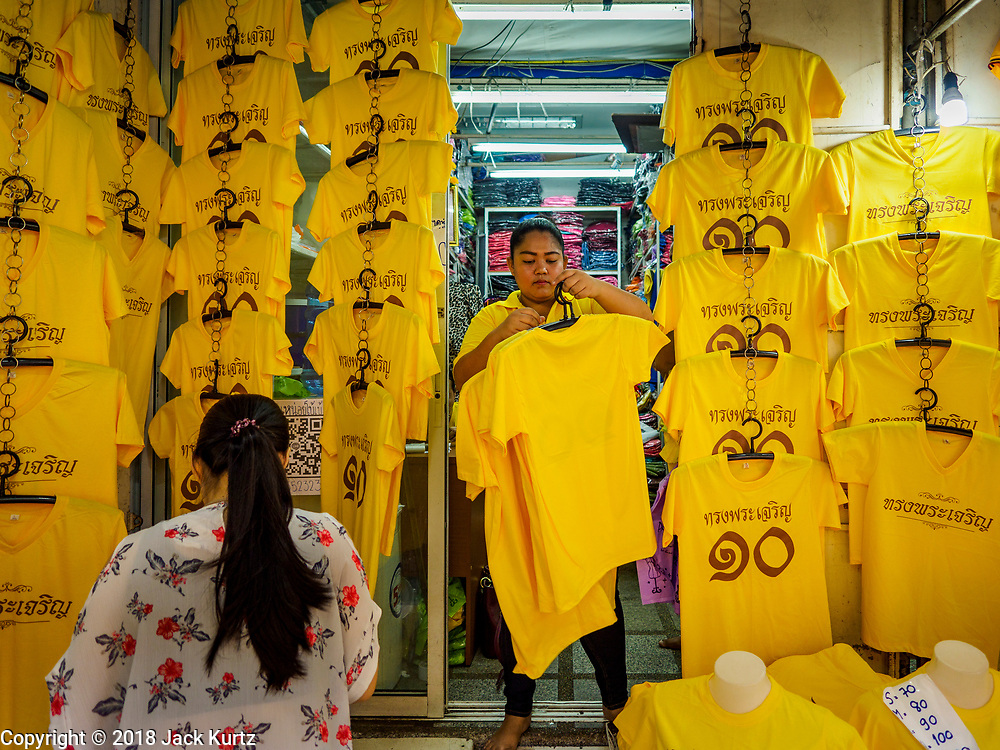 """03 JULY 2018 - BANGKOK, THAILAND: A woman buys yellow shirts that say """"Long Live the King"""" from a vender in Bobae Market in Bangkok. The birthday of King Maha Vajiralongkorn Bodindradebayavarangkun, Rama X, is 28 July. The King, the only son of Thailand's late King Bhumibol Adulyadej, became the King of Thailand in 2016 after the death of his father. King Vajiralongkorn was born on 28 July 1952, a Monday. In Thai culture each day of the week has a color, and yellow is the color is associated with Monday, so people wear yellow for the month before his birthday to honor His Majesty.    PHOTO BY JACK KURTZ"""
