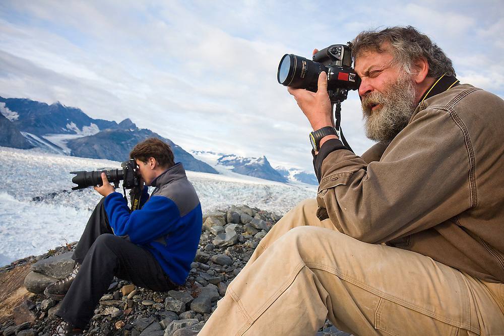 Dr. Tad Pfeffer, a glaciologist with the University of Colorado, and photographer James Balog, of the Extreme Ice Survey, photograph a calving event from camp at Columbia Glacier, Chugach Mountains, Alaska.