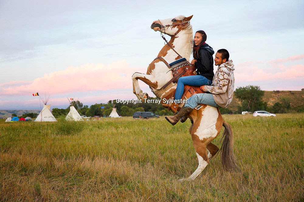 Stevana Salazar (left) of the Kickapoo Tribe of Texas rides with Arlo Standing Bear, Oglala Lakota from Allen, South Dakota, in the resistance camp against the Dakota Access oil pipeline on August 26, 2016. Cannon Ball, North Dakota, United States.