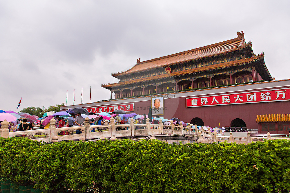 Tourists sheltering under umbrellas stream into the Forbidden City during a rainy summer day in Beijing, China