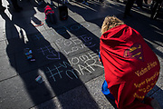 SAN FRANCISCO, CA - JANUARY 20, 2018: A demonstrator writes on the ground in chalk at the Embarcadero, after completing the Women's March in Oakland, California on January 20, 2018. (Photo by Philip Pacheco)