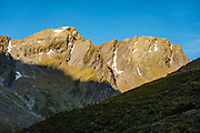 Sunset shines on peaks of the Southern Alps at the headwaters of Rees River at Shelter Rock Hut on Rees-Dart Track in Mount Aspiring National Park, Otago region, South Island of New Zealand.