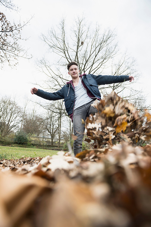 Young man kicking pile of autumn dry leaves on field, Munich, Bavaria, Germany