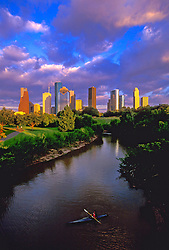 Man kayaking on Buffalo Bayou on the west side of the Houston, Texas skyline.