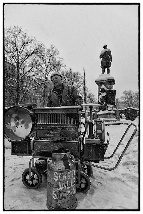 """A barrel organ player in Helsinki, Finland. The artist is blind and in the bin reads """"soup to the player""""."""