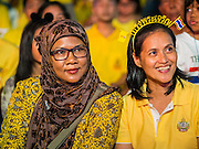 05 DECEMBER 2014 - BANGKOK, THAILAND:  A Muslim woman, left, and Buddhist woman on Sanam Luang for the celebration of the King's Birthday. Thais marked the 87th birthday of Bhumibol Adulyadej, the King of Thailand, Friday. The King was born on December 5, 1927, in Cambridge, Massachusetts. The family was in the United States because his father, Prince Mahidol, was studying Public Health at Harvard University. He has reigned since 1946 and is the world's currently reigning longest serving monarch and the longest serving monarch in Thai history. Bhumibol, who is in poor health, is revered by the Thai people. His birthday is a national holiday and is also celebrated as Father's Day. He is currently hospitalized in Siriraj Hospital, recovering from a series of health setbacks.    PHOTO BY JACK KURTZ