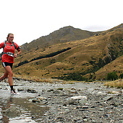 Runner Johanna Jackson crosses Moke Creek on the Ben Lomond High Country Station during the Pure South Shotover Moonlight Mountain Marathon and trail runs. Moke Lake, Queenstown, New Zealand. 4th February 2012. Photo Tim Clayton