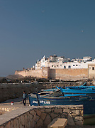 Fishing boats moored at the dock near the fortified sea wall protecting the medina at Essaouira, Morocco