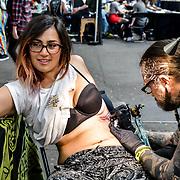 Fiumax & Kila tattoo, Tattoo a client at The Great British Tattoo Show, on 26 May 2019, London, UK.
