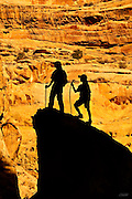 AJ (age 10) and LB (age 8) pause to gaze at the morning light reflecting off the surrounding cliffs while hiking through Crack Canyon in Utah.