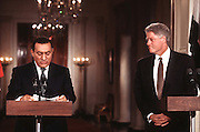 US President Bill Clinton listens to Egyptian President Hosni Mubarak during a joint news conference July 31, 1996 in the White House East Room.