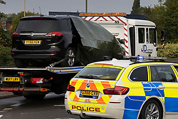 © Licensed to London News Pictures. 28/09/2021. Tongham, UK. A partially covered vehicle (L) is removed on a tow truck from the closed A331 near Tongham in Surrey where a body was found on the carriageway overnight. A police statement says 'We were called to the A331 near the Ash bridge shortly after midnight following reports that the body of a woman had been found in the carriageway. It is believed she was struck by at least five vehicles and enquiries remain ongoing to identify these vehicles. The road is currently closed in both directions while we deal with the incident. Photo credit: Peter Macdiarmid/LNP