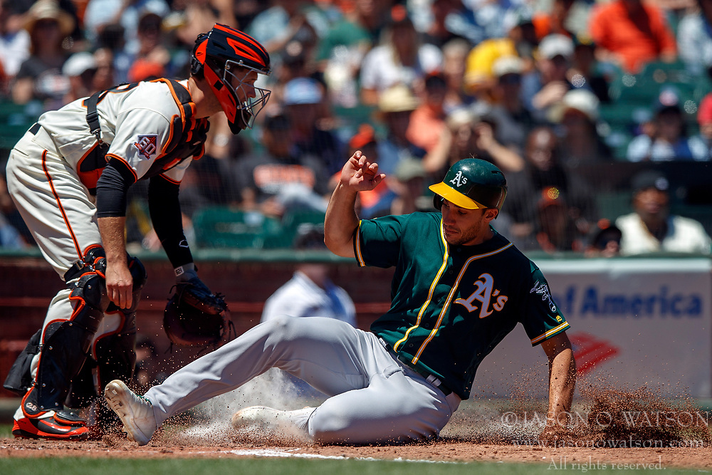 SAN FRANCISCO, CA - JULY 15: Matt Olson #28 of the Oakland Athletics slides into home plate to score a run past Buster Posey #28 of the San Francisco Giants during the fourth inning at AT&T Park on July 15, 2018 in San Francisco, California. The Oakland Athletics defeated the San Francisco Giants 6-2. (Photo by Jason O. Watson/Getty Images) *** Local Caption *** Matt Olson; Buster Posey