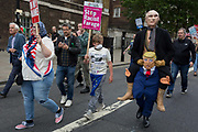 On US President Donald Trumps second day of a controversial three-day state visit to the UK, figures of Russian President Vladimir Putin being given a piggyback on Trump, march alongside protesters voicing their opposition to the 45th American President, down Whitehall, on 4th June 2019, in London England.