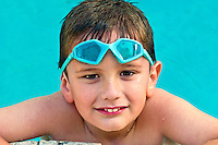 Portrait of a kid enjoying the summer in a swimming pool.