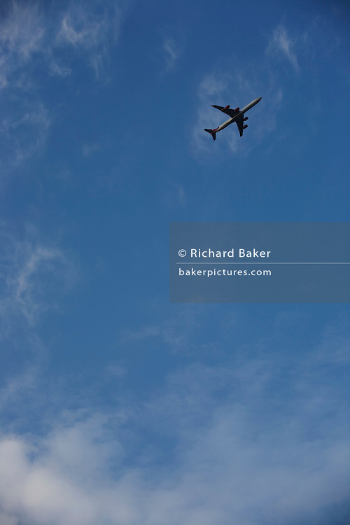 In the top-right corner of the image, an airliner passes overhead in the clear blue sky flight-path over South London