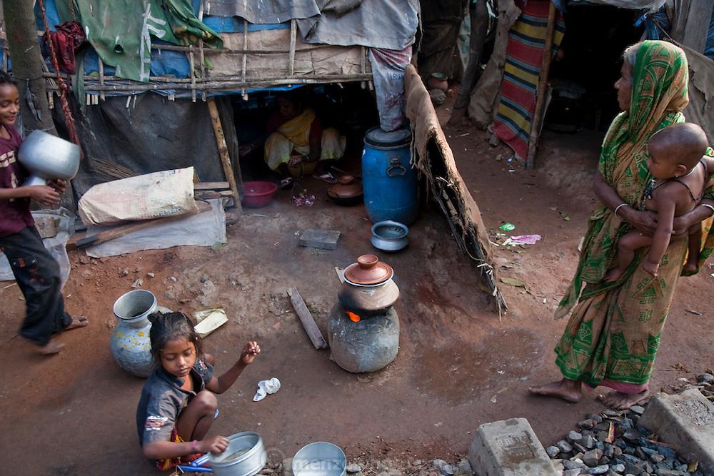A woman carries a child outside a shack in a slum settlement near the main train station in Dhaka, Bangladesh.