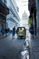 Coco taxi driver waits to get paid in Old Havana.