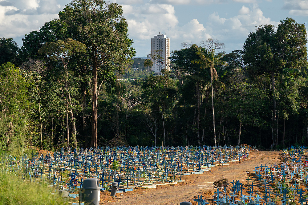 """Blue grave markers called """"Castilhos"""" are laid out for people who died of Covid at Nossa Senhora Aparecida public cemetery March 30, 2021 in Manaus, Brazil. This entire area was all jungle last year but had to be cleared for the thousands that are dying of Covid. Plants are already growing back as the family members are not allowed in to maintain the grave sites. Brazilian residences are receiving the CoronaVac vaccine, also known as the Sinovac COVID-19 vaccine. CoronaVac is an inactivated virus COVID-19 vaccine developed by the Chinese company Sinovac Biotech and has been in Brazil's Phase III clinical trials. Photo Ken Cedeno"""