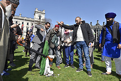 April 18, 2018 - London, UK - LONDON, UK. Kashmiri and Sikh demonstrators set fire to the Indian flag in Parliament Square in protest against the regime of Indian Prime Minister Narendra Modi.  Sikhs, Kashmiri muslims and other groups all had their own message against PM Modi who is visiting London to take part in the Commonwealth Heads of Government 2018 summit. Parliament Square has been decorated with flags of countries of the Commonwealth. (Credit Image: © Stephen Chung/London News Pictures via ZUMA Wire)