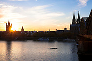 the river Rhine and the old part of the town with the romanesque church Gross St. Martin, the cathedral and the Hohenzollern bridge, sunset, Cologne, Germany.<br />
