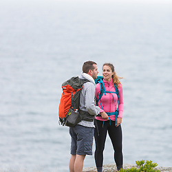 A couple hiking on a cloudy morning on Great Head in Maine's Acadia National Park.