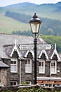 Signpost to Capel Curig and Caernarfon with Welsh slate roofs and mountains backdrop, Beddgelert, Gwynedd, Wales
