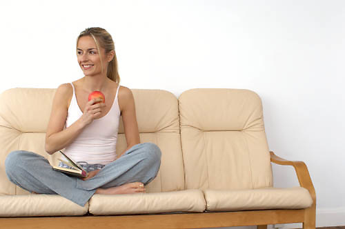 women sitting crossed legged on a sofa reading a book and holding an apple<br />