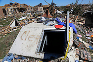 The two-week-old storm shelter that saved 9 people is surrounded by destroyed homes in Oklahoma City, Oklahoma May 22, 2013. Rescue workers with sniffer dogs picked through the ruins on Wednesday to ensure no survivors remained buried after a deadly tornado left thousands homeless and trying to salvage what was left of their belongings.  REUTERS/Rick Wilking (UNITED STATES)