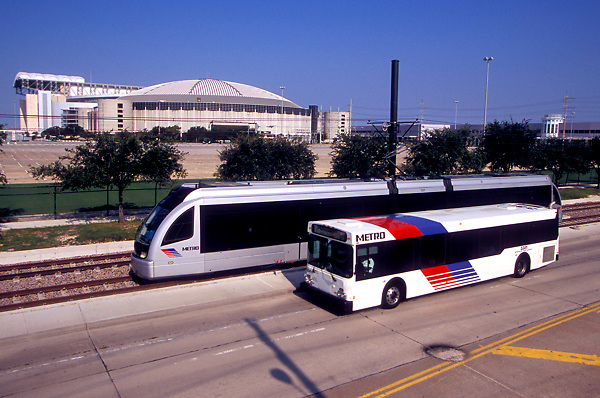 Houston Metro bus and light rail run in front of Reliant Stadium and the Astrodome