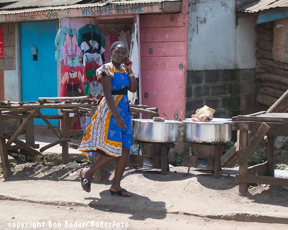 Kenyan woman walking down road in front of clothing and food shops in Nairobi Kenya's Kibera Slum