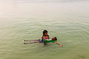 Young children play in the waters of New Plymouth bay on Green Turtle Cay, Bahamas.