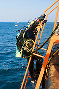 "Israel, Bay of Haifa, Offshore rig salvages the remains of the Israeli cargo vessel ""Shelly"" that sunk 3km from the harbour after a collision with a passenger ship on August 31 2007. Commercial diver coming out of the Mediterranean sea. Cables from the surface are supplying electrical power for the lights, and allowing communication with the surface. The diver is using a helmet connected to an air supply on his back"