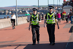 Portobello, Edinburgh. Scotland, UK. 11 April, 2020. Easter bank holiday weekend Saturday afternoon in very warm sunny weather the public are outdoors exercising and walking on Portobello beach. The popular beach and promenade was very quiet and people were mostly exercising proper social distancing. Pictured; Police patrolling the promenade stop to talk to people who are sitting or in groups. They are politely asked to observe the spirit of the Coronavirus lockdown rules and move on. Iain Masterton/Alamy Live News