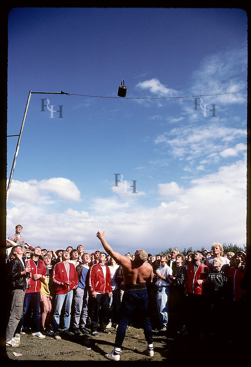 Jon Sigmarsson, winner of 1985 'World's Strongest Man' contest, throws weight high over wire. Iceland